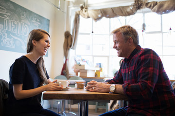 Father And Daughter Sitting At Table In Coffee Shop Together