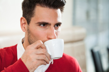 Young man is drinking coffee in a cafe.
