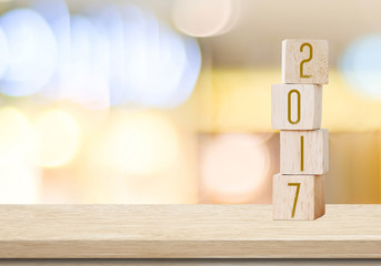 Wooden cubes with 2017 on table over blur bokeh background