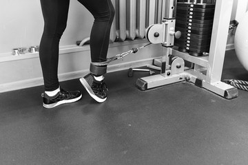 Sports young woman doing exercises in the gym.