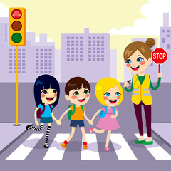 Three cute little children school students crossing street together with help from female teacher holding stop sign