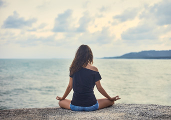 Woman meditating on rocky cliff with sea view