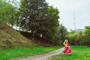 Happy little girl runs on the green grass