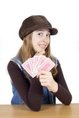Smiling Cute Girl With Playing Cards Touching Her Chin And Looking Into The Camera Isolated On White