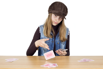 Young Girl Sitting At A Wooden Table And Dealing Playing Cards For The Next Round, Isolated On White
