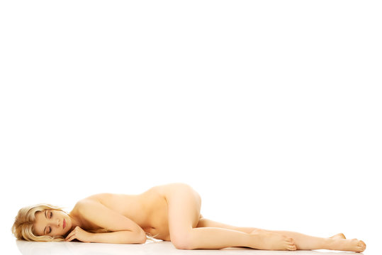 Full length young nude woman lying on the floor