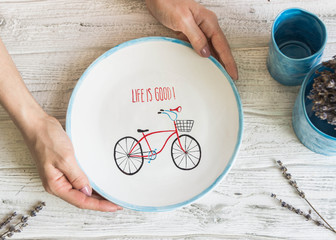 Ceramic handmade plate with a painted bike. Hands in the frame. Copyspace