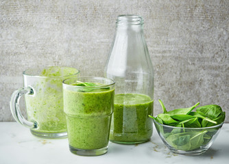 glass and bottle of green smoothie