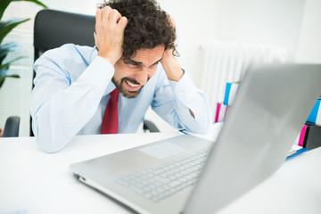 Angry businessman looking at his computer