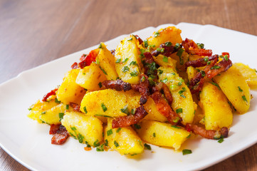 fried potatoes with bacon in a plate on wooden table