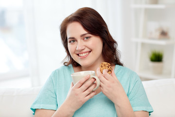 happy plus size woman with cup and cookie at home