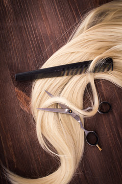 Hairdressing Scissors with blonde hair on a brown wooden background.