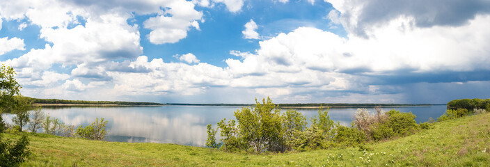 Bright, beautiful panorama of of the river on a sunny day with clouds.
