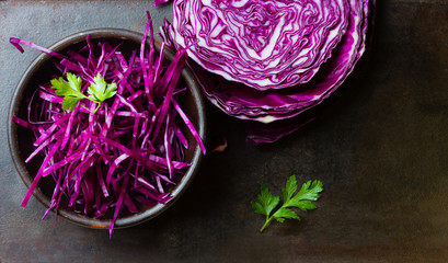 Shredded red cabbage in clay bowl. Background. Top view