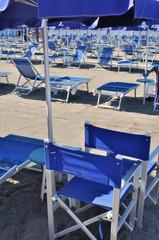 chaises de plage et parasol bleus sur une plage d'Italie
