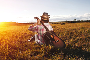 Girl in a hat sits on the field and holds the guitar behind his back.