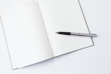 blank book with a pen on top on a white background