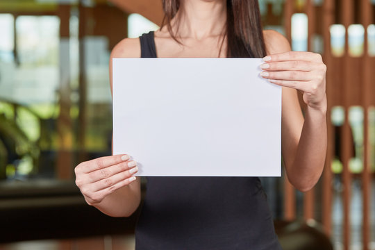 Young caucasian woman holding white sheet of paper