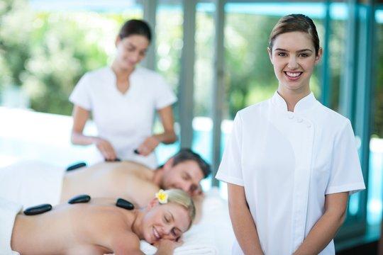 Portrait of happy female masseur in spa