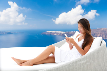 Wall Mural - Asian woman using phone app relaxing on daybed on outdoor terrace. Home living outside patio furniture. Young adult texting on smartphone lying on sofa with Oia Santorini background enjoying summer.