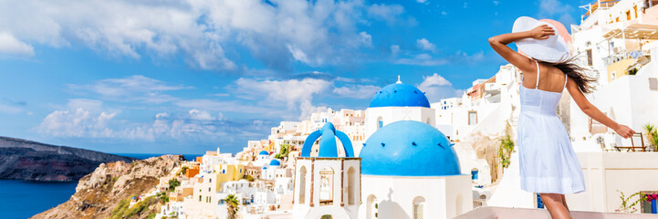 Wall Mural - Europe tourist travel woman panorama banner from Oia, Santorini, Greece. Happy young woman looking at famous blue dome church landmark destination. Beautiful girl visiting the Greek islands.