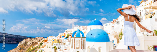 Wall mural Europe tourist travel woman panorama banner from Oia, Santorini, Greece. Happy young woman looking at famous blue dome church landmark destination. Beautiful girl visiting the Greek islands.