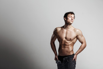 Handsome athletic man looking side in unbuttoned jeans. Strong bodybuilder with six pack, perfect abs, shoulders, biceps, triceps and chest. Great fitness body. Ideal for commercial. Gray background