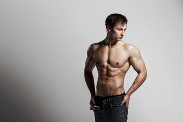 Muscular male model bodybuilder with unbuttoned jeans. Studio shot on gray background. Fitness MODEL. Great for commercial. Ideal fitness body with six pack, perfect abs, shoulders.