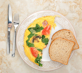omelet with spinach, tomatoes and mushrooms on round plate