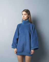 Beautiful long haired blond scandinavian girl wearing a big blue sweater and clips in her hair standing up against a blue wall