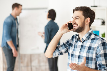 Cheerful male worker is communication on telephone