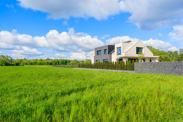 Modern house on green meadow in rural landscape of Krakow, Poland