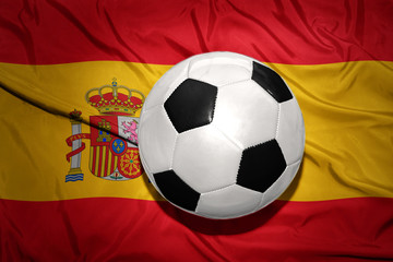black and white football ball on the national flag of spain