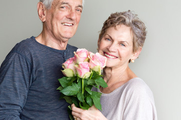 Older woman in beige top holding pink roses smiling with older man in blue top.