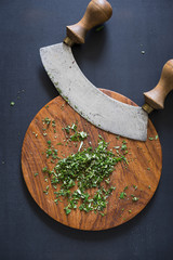 Italian traditional old mezzaluna knife and chopped herbs on cutting board