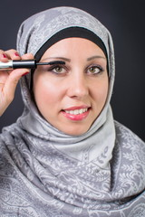 Muslim woman applying mascara