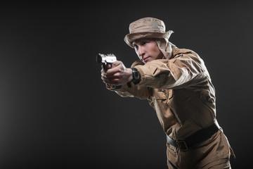 Soldier with a gun takes aim on dark background