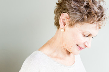 Profile view of older woman in beige top looking down thoughtfully