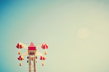 Vintage amusement park ride over blue sky