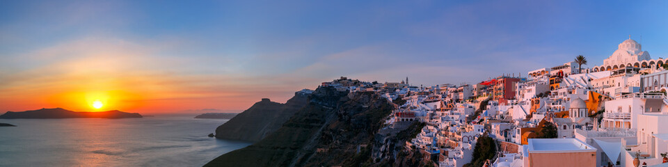 Picturesque panorama of Fira, main town of the island Santorini, sea, white houses and church at sunset, Greece
