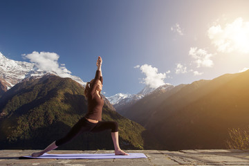 Morning Exercises in mountains landscape. Young Woman doing Yoga outdoor