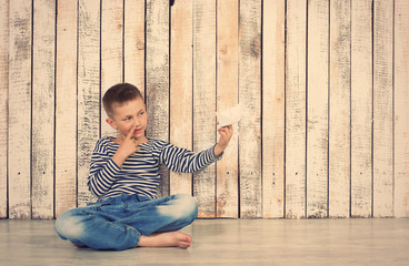 Boy sitting with paper boat indoor, playing and dream about to be a sailor