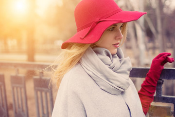 attractive young woman with elegant red hat and gloves walking outdoor in spring sunny day