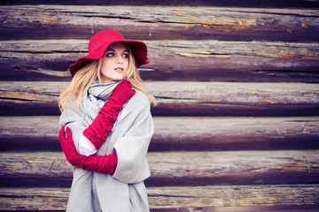 attractive young woman with elegant red hat and gloves neat old wooden house wall