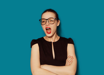 Studio expression portrait of young attractive screaming girl in glasses on blue background