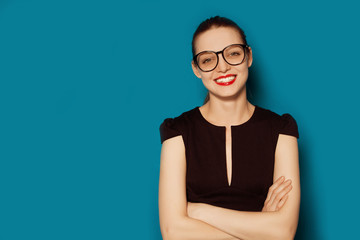 Smiling beautiful young woman in glasses. Business studio portrait on blue background