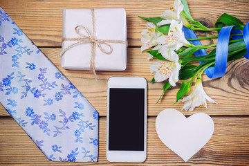 Tie, gift box, flowers with ribbon, cell phone on wooden table