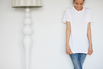 Human face expressions and emotions. Cropped portrait of attractive young female with happy smile posing in white blank copy space T-shirt for your advertising content against white studio wall.