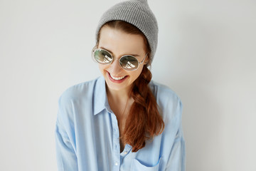 Stylish smiling young female. Portrait of fashionable student girl wearing round sunglasses going for a walk with her friends after classes at university. Human face expressions and emotions