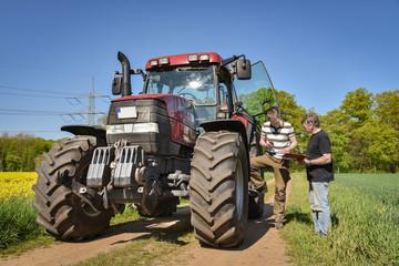 Landwirtschaft - Landwirt mit seinem Sohn bei einer Besprechung am Traktor
